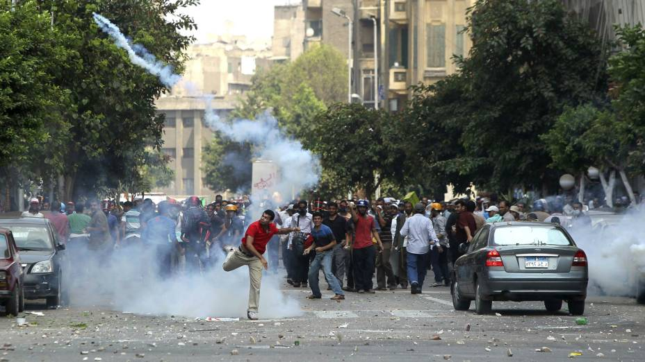 Manifestante arremessa bomba de gás lacrimogêneo disparada contra marcha pró-Mursi, no Cairo