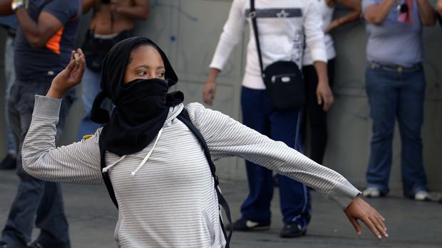Manifestante joga pedra durante protesto contra o governo da Venezuela