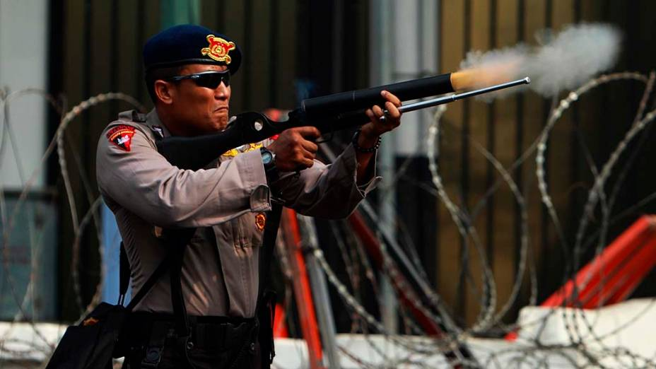 Policial atira latas de gás lacrimogênio para conter protestos em frente à embaixada americana em Jacarta, Indonésia