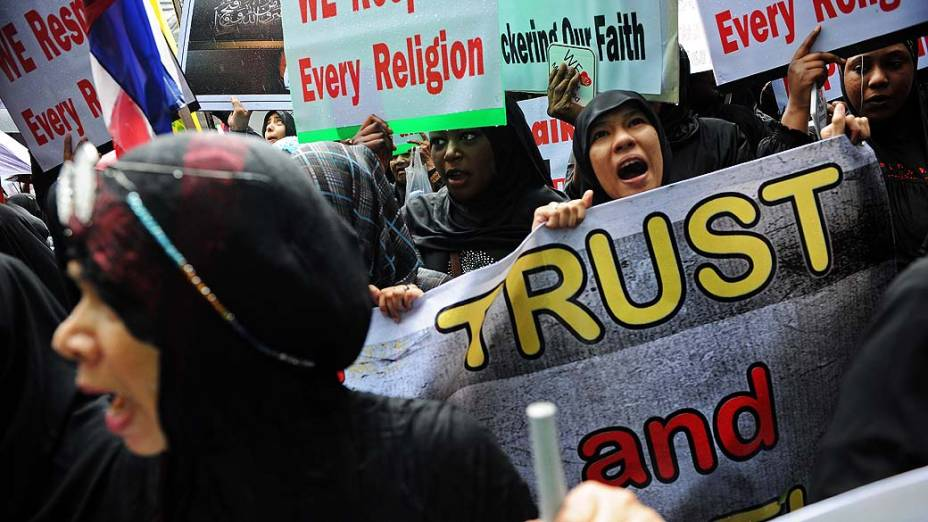 """Manifestantes em protesto anti-EUA seguram cartazes com os dizeres """"Nós respeitamos todas as religiões"""" em Bangcoc, Tailândia"""