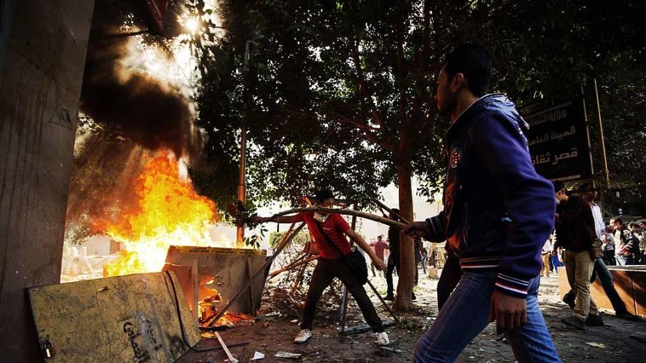 Manifestantes alimentam fogueira em confronto com a polícia durante protesto contra novas determinações do presidente do Egito, Mohamed Mursi