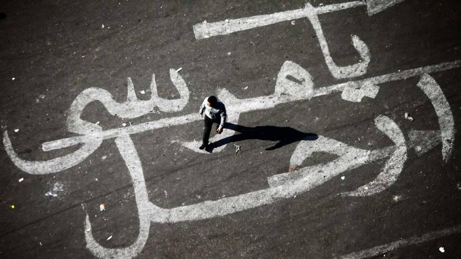 Homem caminha sobre pintura em asfalto com a mensagem Mursi, vá embora, em uma referência ao presidente egípcio, membro da Irmandade Muçulmana