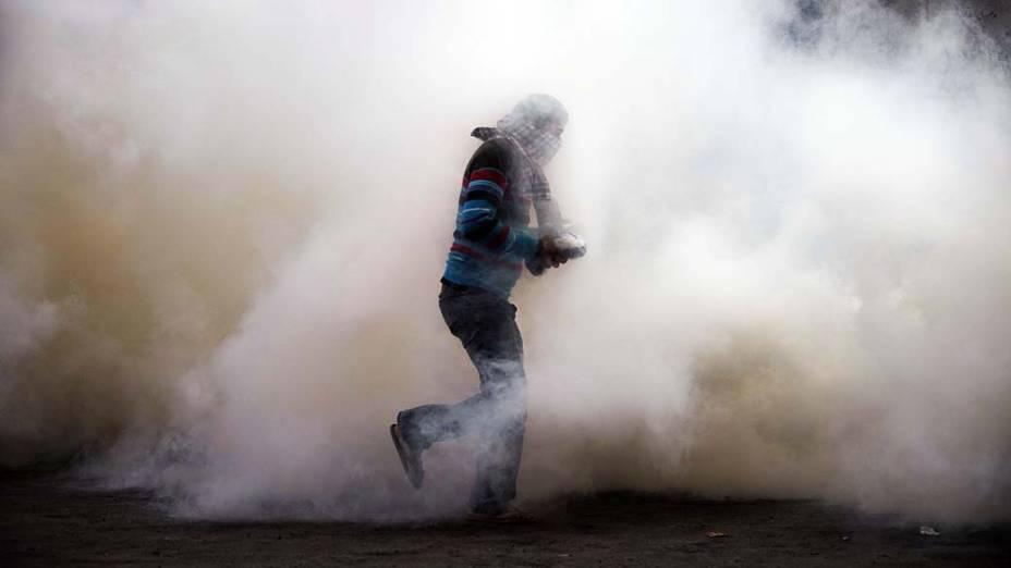 Manifestante em meio a fumaça durante confronto com policiais perto da Praça Tahrir, no Cairo, Egito