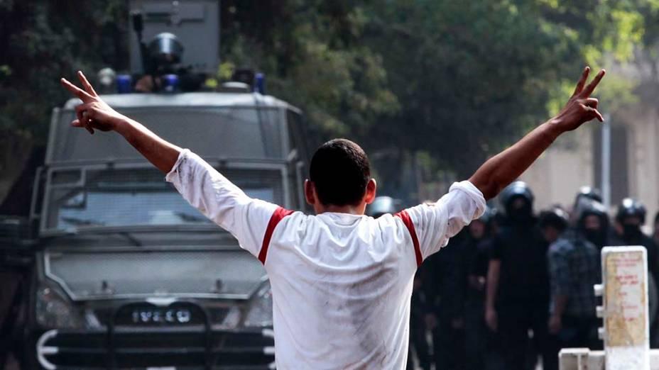 Manifestante enfrenta policiais durante confronto próximo à Praça Tahrir, no Cairo, Egito