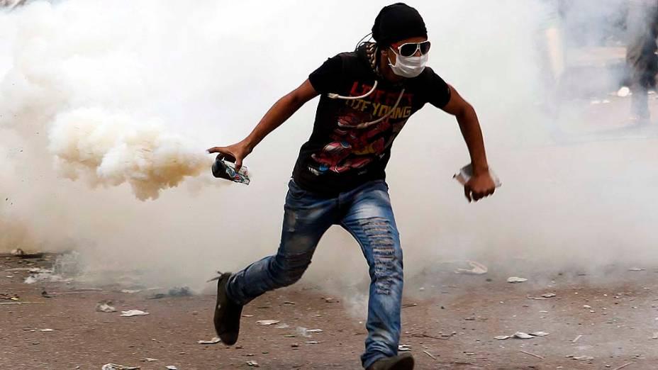 Manifestante contrário ao presidente Mohamed Mursi segura lata de gás lacrimogênio durante confronto com a polícia perto da Praça Tahrir, no Cairo