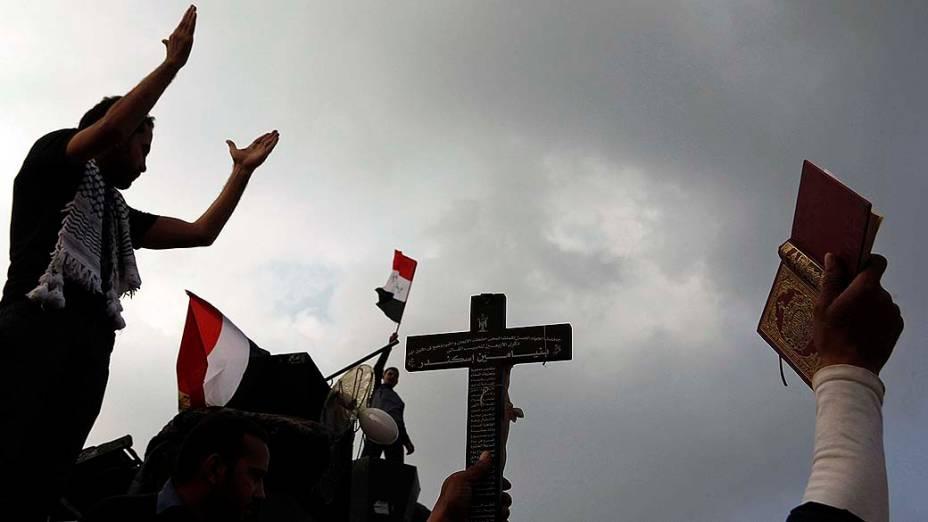 Na Praça Tahir, manifestante segura uma cruz e o livro do Corão, durante protesto contra decreto que aumenta poderes do presidente Mohamed Mursi
