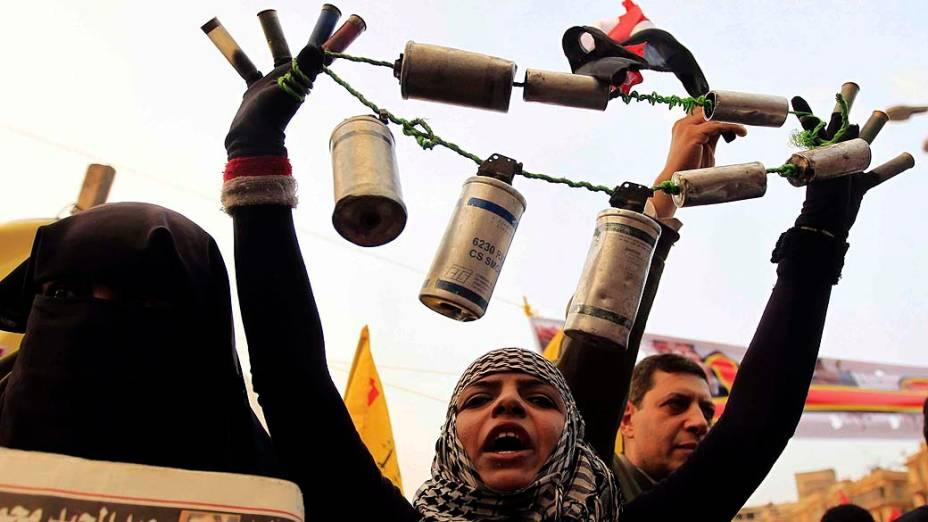 Mulher exibe latas de gás lacrimogênio e balas de borracha usadas pela polícia durante manifestação na Praça Tahrir, no Cairo