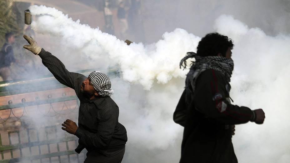 Manifestantes com bomba de gás durante confronto com policiais, na Praça Tahrir