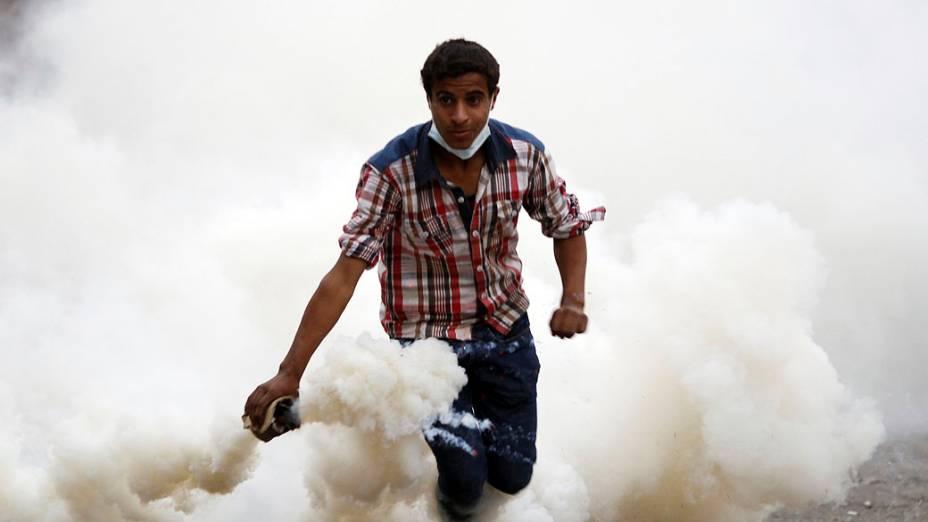 Manifestante joga bomba de gás durante confronto com policiais, próximo da Praça Tahrir