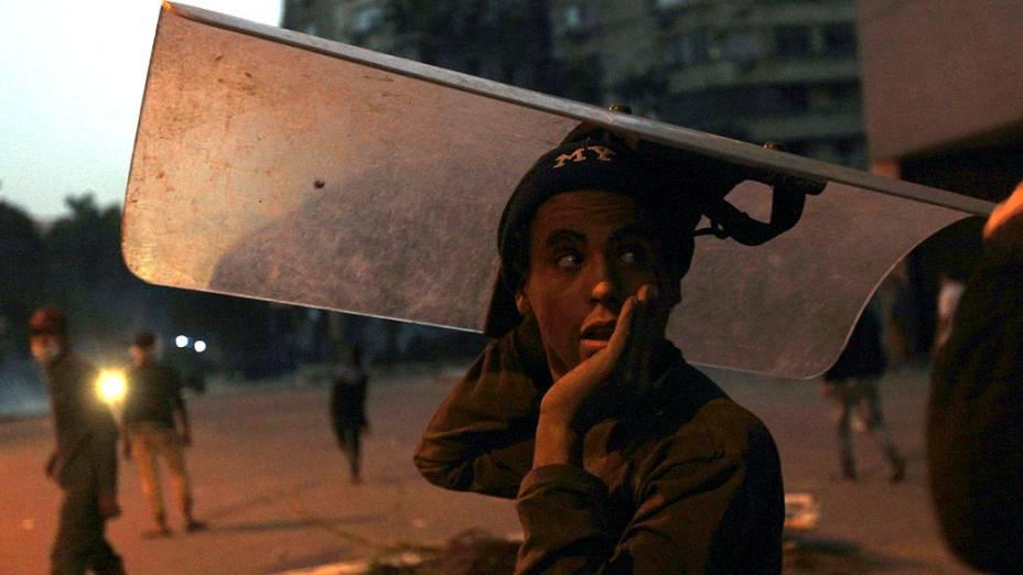 Manifestante com escudo de policial durante confronto perto da Praça Tahrir, no Cairo