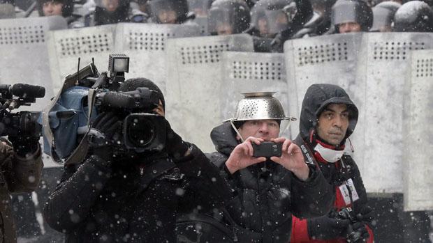 Repórteres durante confrontos entre manifestantes e a polícia, em Kiev