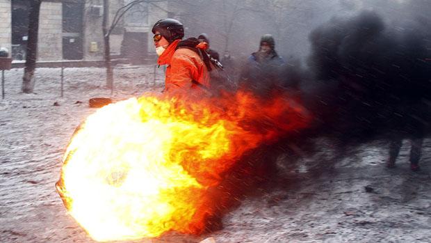 Homem carrega pneu em chamas durante confronto no centro de Kiev, na Ucrânia