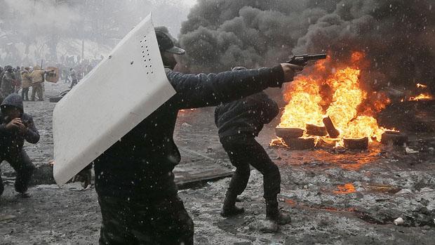 Manifestante aponta arma contra policiais, em Kiev