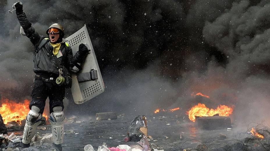 Manifestante entre pneus em chamas e detritos no centro de Kiev, na Ucrânia