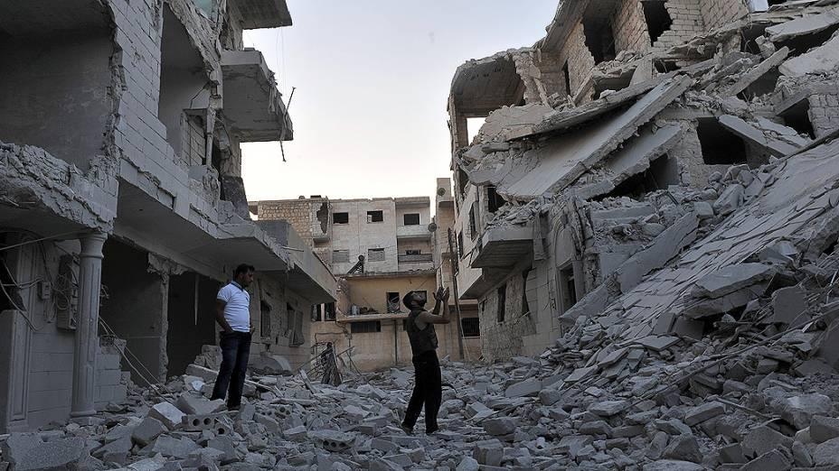 Pessoas rezam sobre as ruínas de prédio bombardeado pela Força Aérea Síria na cidade de Maaret al-Numan, no noroeste do país, região sob controle do exército rebelde