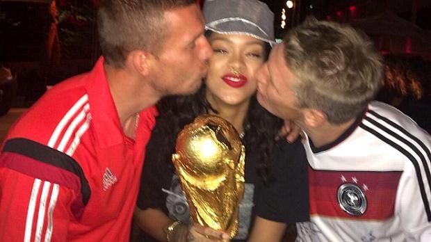 Rihanna segura a taça com os jogadores alemães Podolski e Schweinsteiger