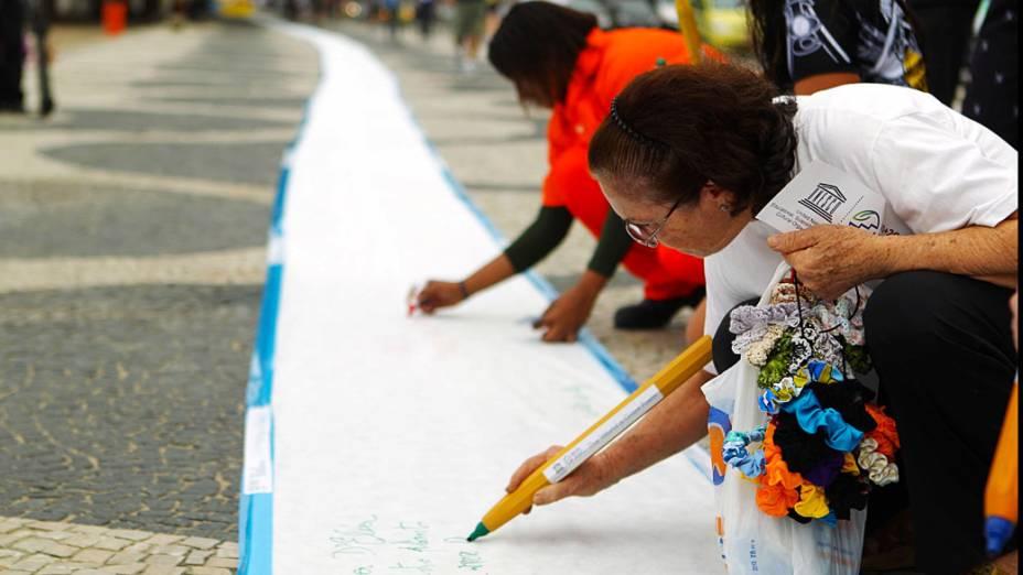 Pessoas escrevem o poema gigante, na Praia de Copacabana