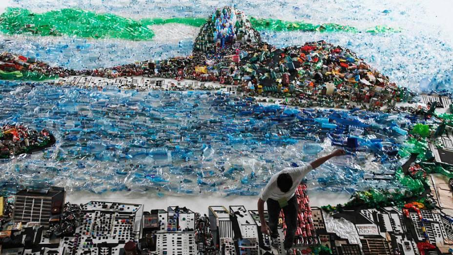 Homem dá retoques finais na imagem da Baía de Guanabara feitas de lixo reciclado, parte de uma instalação do artista brasileiro Vik Muniz, durante a Rio +20