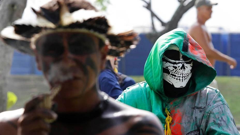 Homem fantasiado próximo de um indígena durante a Cúpula dos Povos na Rio +20, no Rio de Janeiro