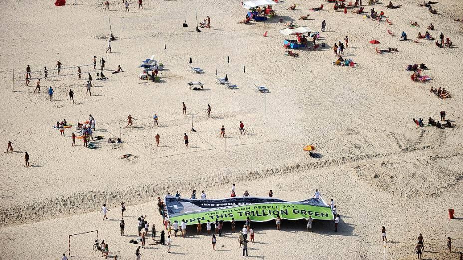 Ambientalistas exibem faixa em que pedem o fim de subsídios para a produção de combustíveis fósseis, na praia de Copacabana