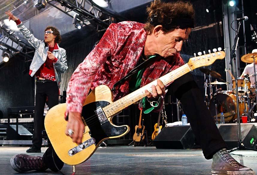 O guitarrista Keith Richards e o vocalista Mick Jagger ao fundo durante show de 2003 em Munique, Alemanha
