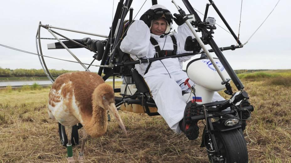 O presidente russo, Vladimir Putin, se senta em um deltaplano motorizado perto de uma cegonha no distrito de Yamalo-Nenets