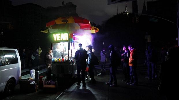 Mesmo sem energia elétrica na rua, carrinho de cachorro quente não deixou de atrair clientes em NY