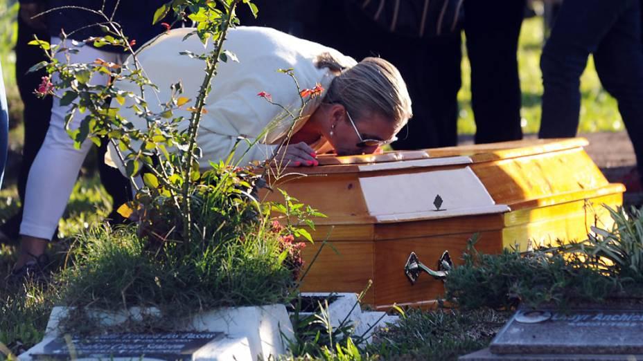 Lívia Oliveira, mãe de Heitor, beija seu caixão durante funeral, em cemitério de Santa Maria