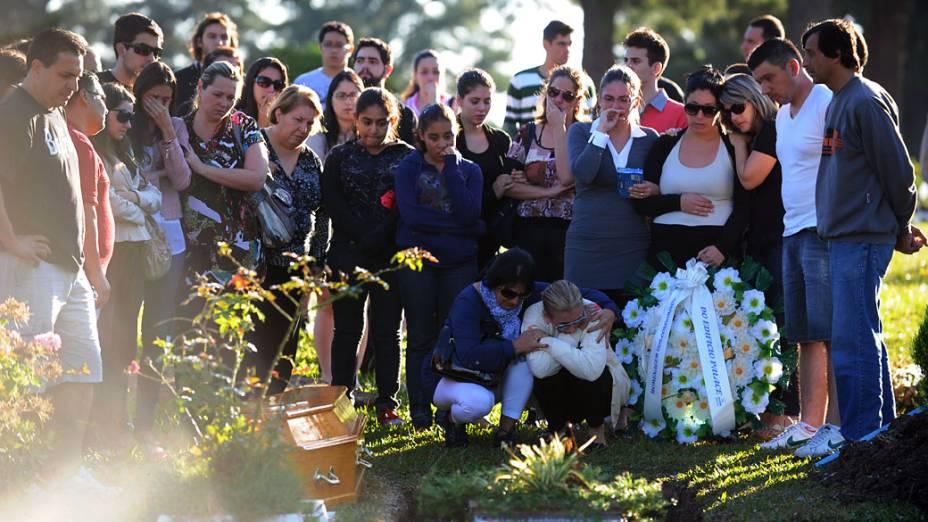Parentes e amigos de Heitor de Oliveira se reunem em torno de seu caixão durante o funeral no cemitério de Santa Rita em Santa Maria