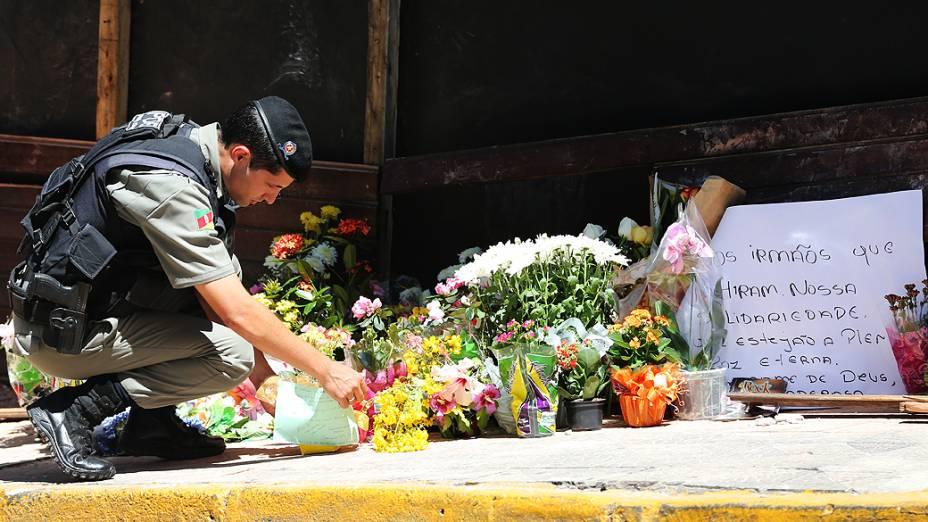 Policial coloca flores em homenagem às vítimas em frente a boate em Santa Maria (RS)