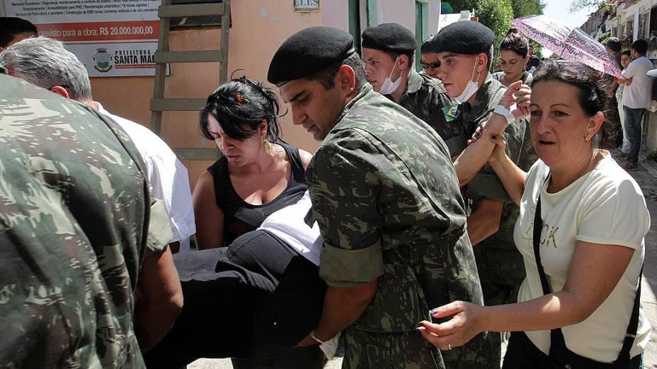 Mulher passa mal durante o enterro de Neiva de Oliveira, uma das vítimas do incêndio na boate Kiss, no Cemitério Municipal de Santa Maria (RS), nesta segunda-feira (28)