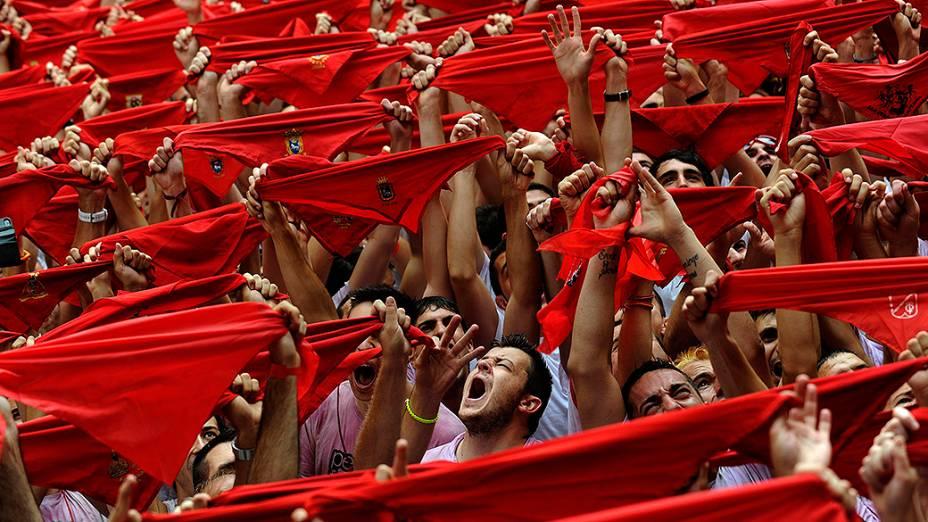 Centenas de pessoas seguram lenços vermelhos que fazem parte da tradicional vestimenta do Festival de São Firmino, que ocorre anualmente na cidade histórica de Pamplona, na Espanha, entre os dias 06 e 14 de julho