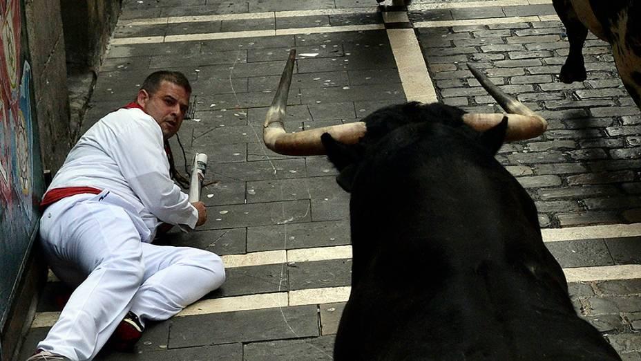 Na imagem, folião é visto em frente a um touro durante a primeira corrida do Festival de São Fermino, na cidade de Pamplona, Espanha. A corrida, originalmente chamada encierro, é uma das atividades mais famosas do festival e percorre 850 metros por três ruas do centro histórico da cidade