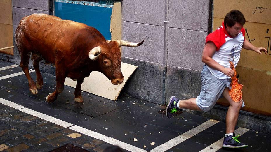 Homem corre de um touro durante o festiva de São Firmino em Pamplona, na Espanha