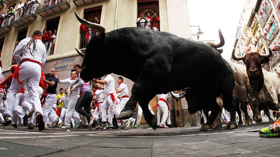 Homens participam da tradicional corrida de touros durante o festival de São Firmino em Pamplona, na Espanha