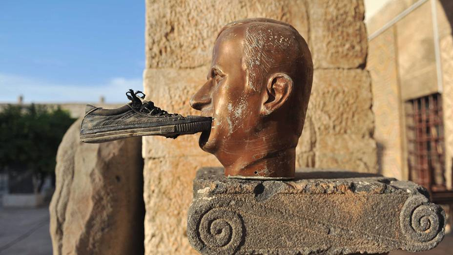 Um sapato é colado na boca de uma estátua do falecido presidente da Síria Hafez al-Assad, no museu de Maaret al-Numan
