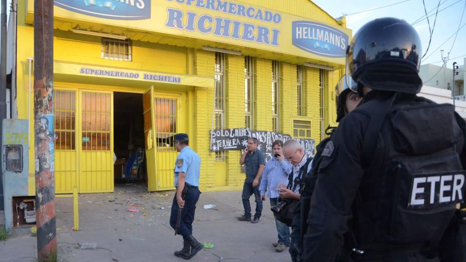 Policiais na entrada de supermercado saqueado, em Córdoba