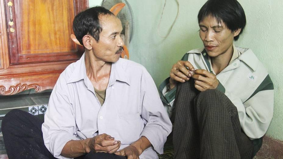 Homem conversa com Ho Van Lang (dir), de 42 anos. Ele passou 40 anos na selva vietnamita sem ter contato com o mundo exterior.