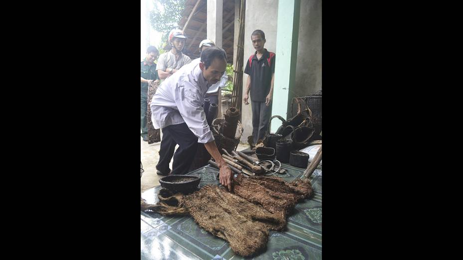 Homem pega em uma das vestimentas que dois sobreviventes da Guerra do Vietnã fizeram com cascas  de árvores