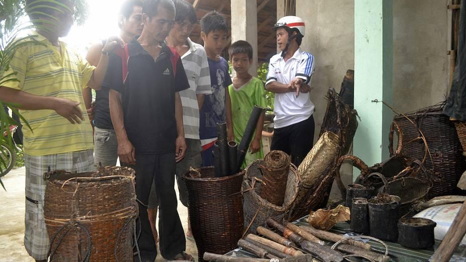 Curiosos observam os instrumentos utilizados pelos sobreviventes da Guerra do Vietnã que passaram 40 anos na selva