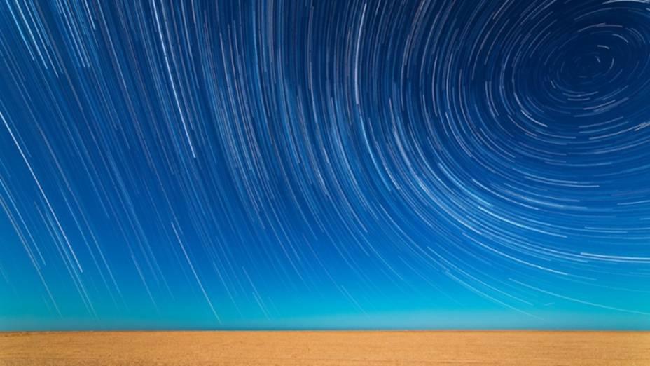 <p>Diversas imagens foram sobrepostas para produzir o efeito time-lapse. A rotação da Terra transforma a luz das estrelas em linhas sobre uma praia na cidade de Mar de Ajó, na Argentina</p>