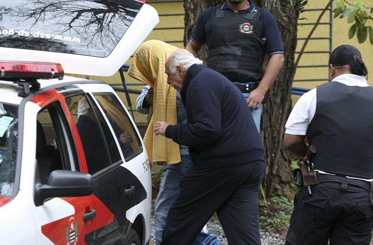 O médico Roger Abdelmassih e outro preso, que esconde o rosto, no IML Central de São Paulo, na terça-feira, pouco antes de serem transferidos para o presídio de Tremembé.