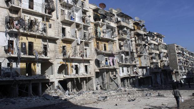As pessoas passam por edifícios danificados em Aleppo