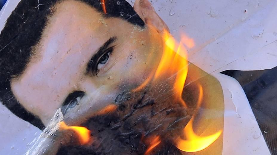 Retrato do presidente sírio, Bashar al-Assad queimando durante confrontos entre rebeldes e as tropas sírias no distrito de Salaheddin norte da cidade de Aleppo