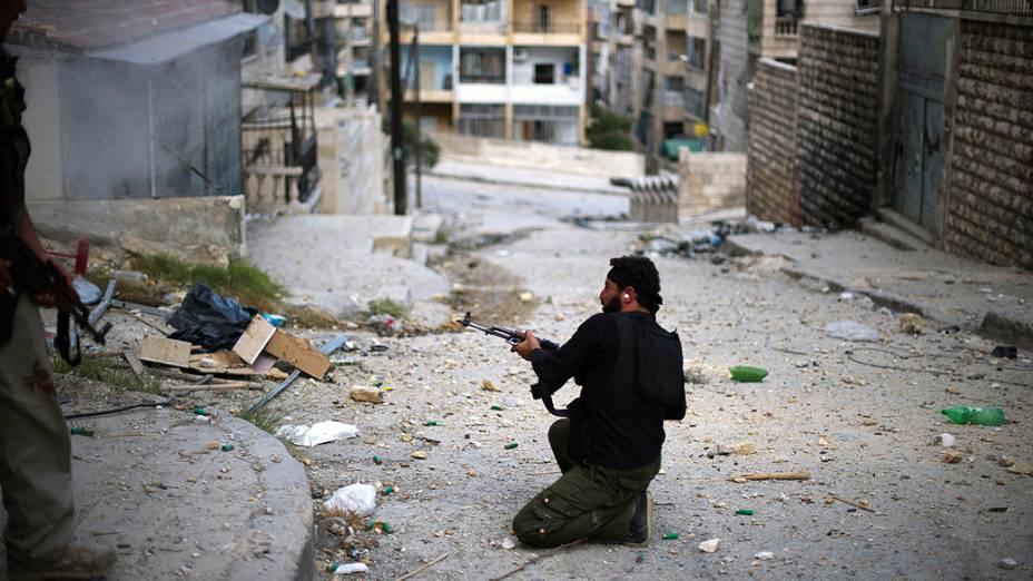 Soldado do Exército Livre da Síria dispara contra forças do regime no disputado bairro de Izza, em Aleppo, no norte do país