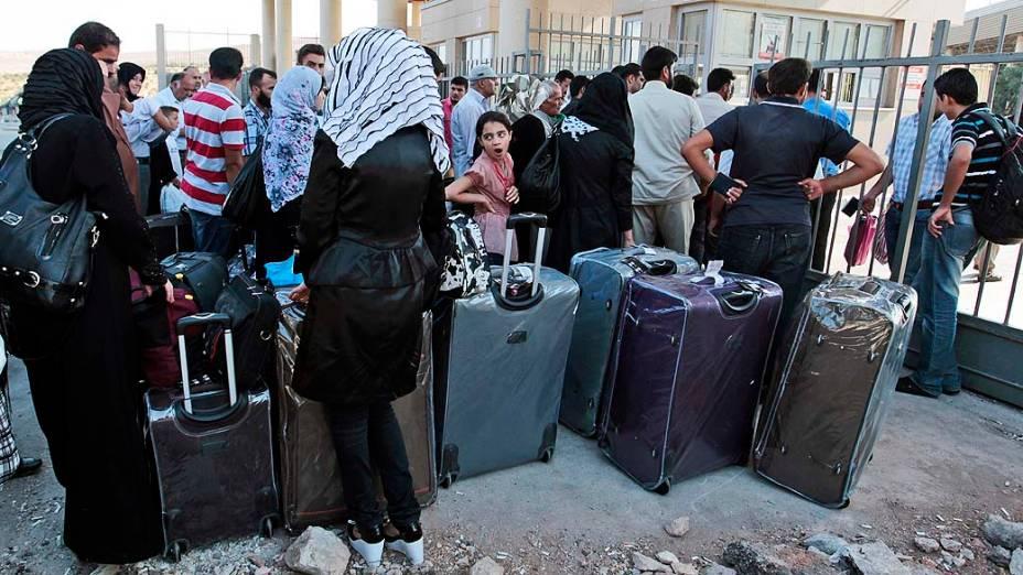 Refugiados sírios fazem fila perto da fronteira com a Turquia para tentar deixar o país. A ONU divulgou na terça-feira (3) que o número de refugiados sírios chegou a 2 milhões