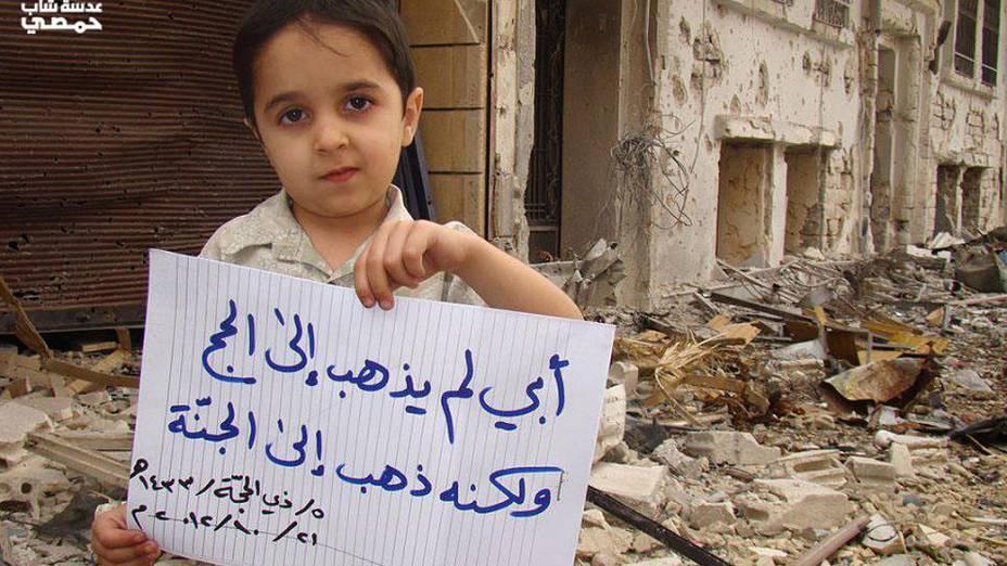 """Menino segura cartaz com dizeres: """"meu pai não foi ao Hajj (peregrinação à Meca), ele foi ao céu (indicando que o pai foi morto pelos bombardeios)"""""""