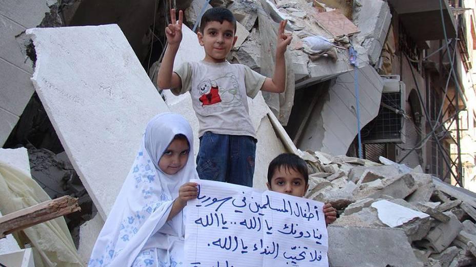"""Crianças seguram cartaz: """"Crianças muçulmanas estão chamando pelo nosso senhor Deus. Mas Deus não está respondendo"""""""