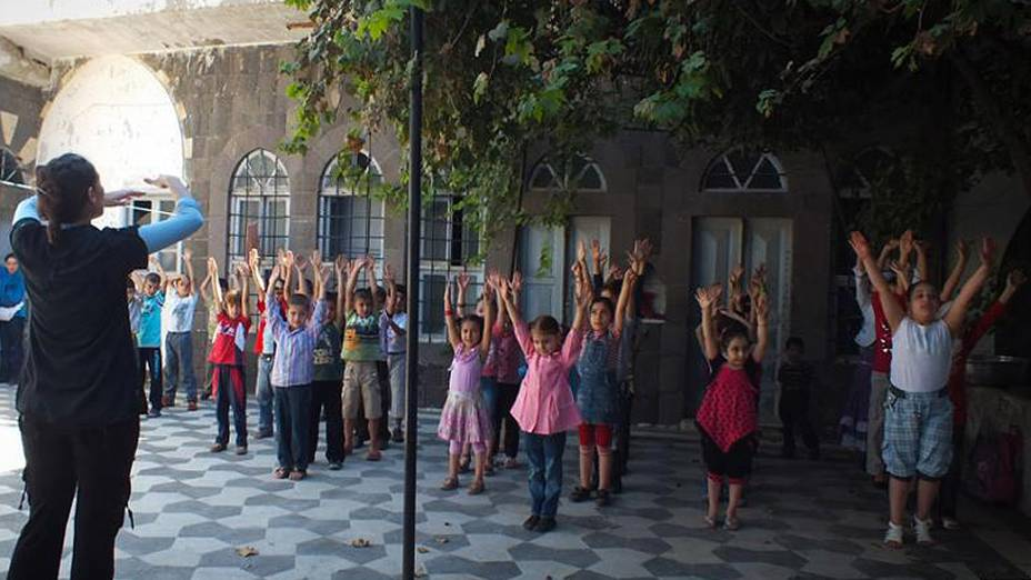 Crianças tentam votlar às aulas apesar da guerra e da cidade de Homs sofrendo bombardeios. No terceiro dia de escola, uma estudante universitária voluntária tenta ajudar por falta de professores