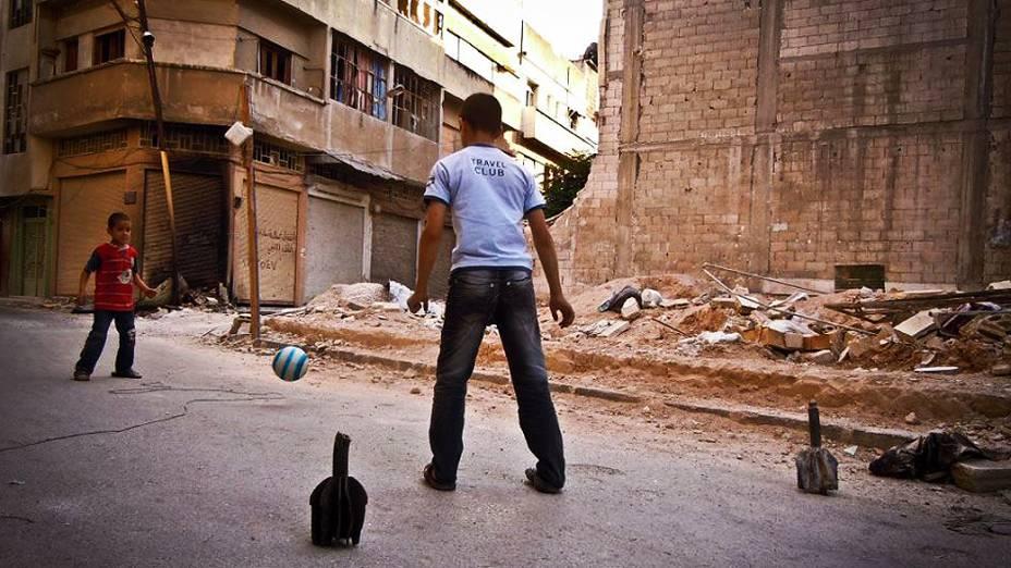 Crianças usam pedaços de morteiros, supostamente disparados por tropas do regime sírio, como goleiras para jogar futebol